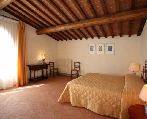 camera con letto matrimoniale e soffitto con travi in legno